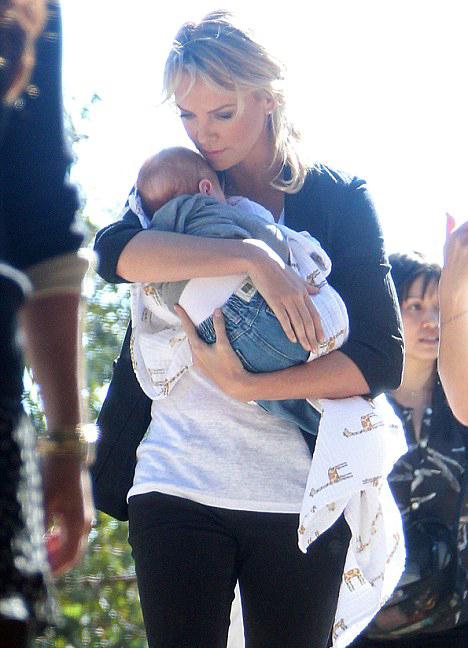 На съемках нового фильма папарацци сфотографировали Шарлиз, которая нянчила сына своей подруги. Уже тогда было заметно, с какой нежностью она держит малыша. Фото: Daily Mail.